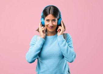 Young student girl with blue sweater listening music on pink background.