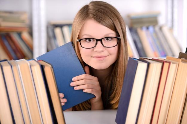 Молодая девушка студента с книжной полкой выбора книги.