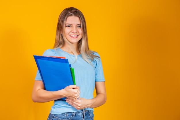 黄色の背景の本を持つ若い学生の女の子。学校に戻る。