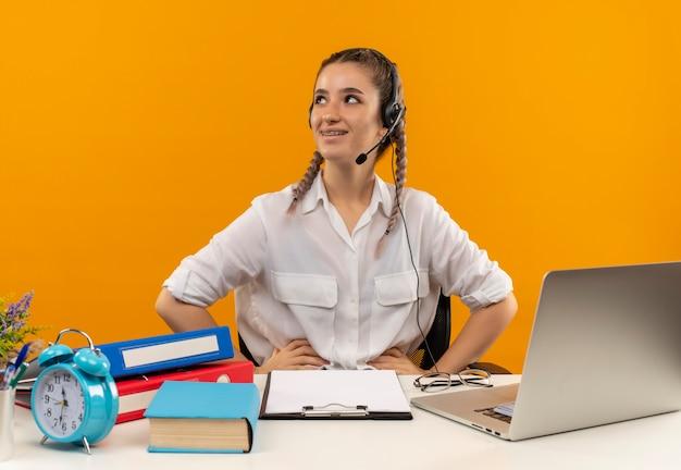 白いシャツのピグテールとマイク付きの若い学生の女の子は、ラップトップフォルダークリップボードとオレンジ色の壁の上の本とテーブルに座って顔に笑顔で脇を見て
