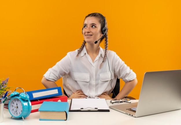 Young student girl with pigtails in white shirt and headphones with microphone looking aside with smile on face sitting at the table with laptop folders clipboard and book over orange wall