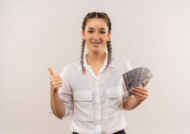 Ragazza giovane studente con trecce in camicia bianca che mostra sorridere in contanti guardando in avanti che mostra i pollici in su in piedi sul muro bianco