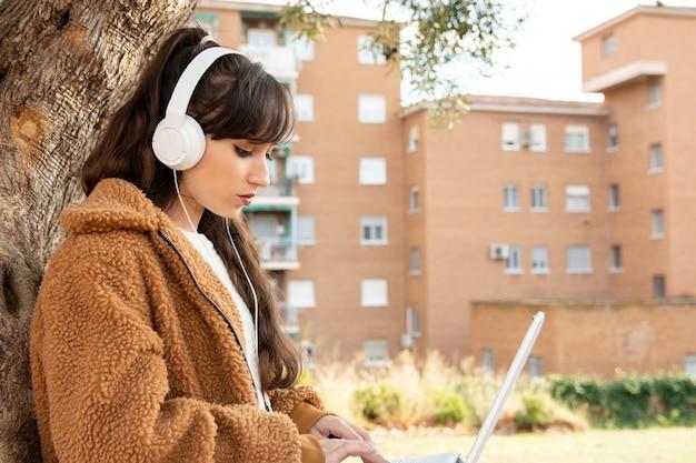 공원에서 그녀의 노트북을 사용하는 젊은 학생 소녀.
