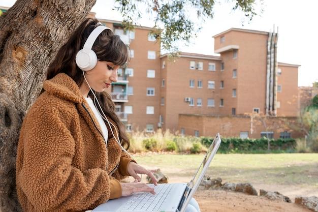 Девушка молодого студента работая с ее компьтер-книжкой в парке.