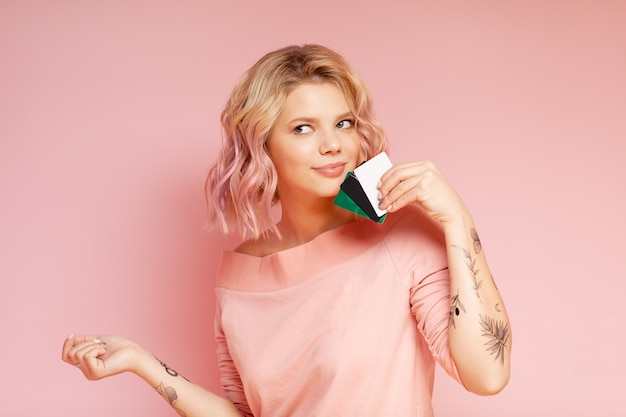 Young student hipster woman with colored hairs and tattoo holding credit cards