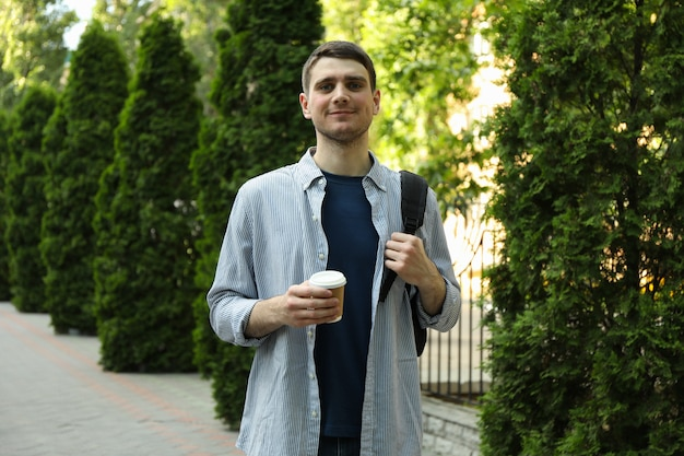Young student hold backpack and cup of coffee.