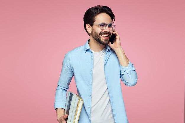 本を持って、ピンクの壁に携帯電話で話す若い学生