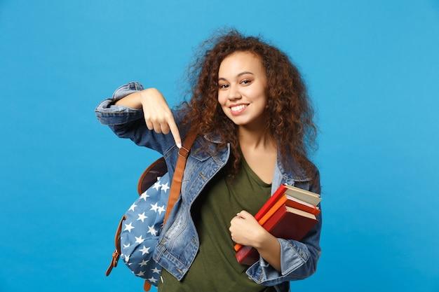 Молодой студент в джинсовой одежде и рюкзаке держит книги, изолированные на синей стене