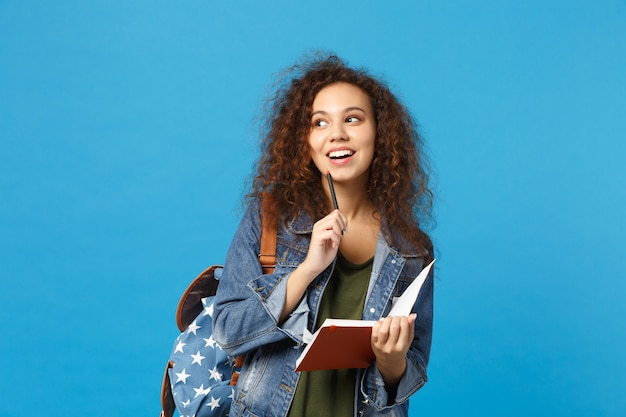 デニムの服とバックパックの若い学生は青い壁に隔離された本を保持します