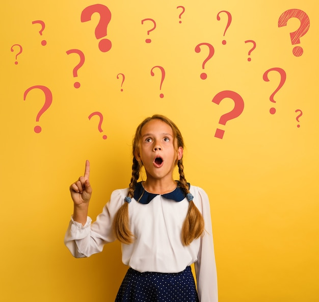 Young student is with shocked expression and indicates a lot of question marks. yellow background