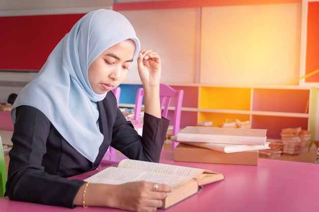 Young student islamic woman. she is sitting and reading book.