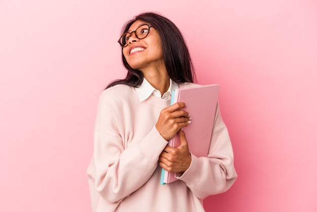 Young student latin woman isolated on pink background dreaming of achieving goals and purposes