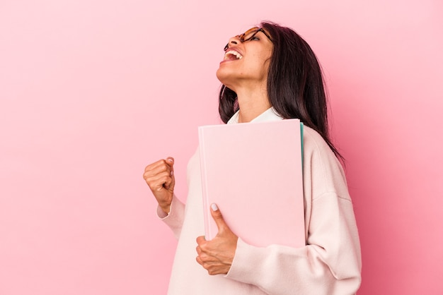 Young student latin woman isolated on pink background raising fist after a victory, winner concept.
