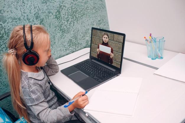 タッチャーを持つ若い学生の少女は、ラップトップ画面の学習と学校に戻る準備を手に二次方程式の白いポスターを保持しています。