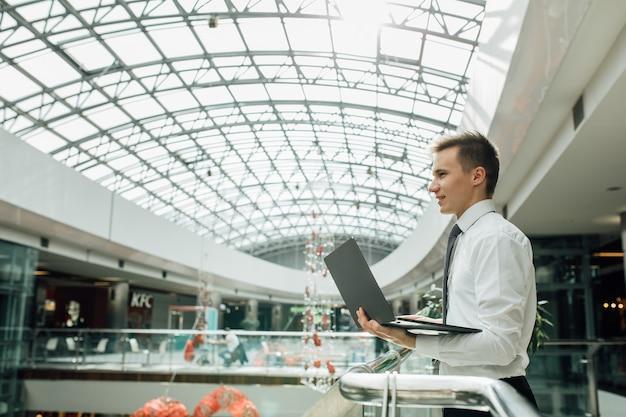 未来を見据えた若い学生、ノートパソコンを手に、白いシャツを着て、モールで