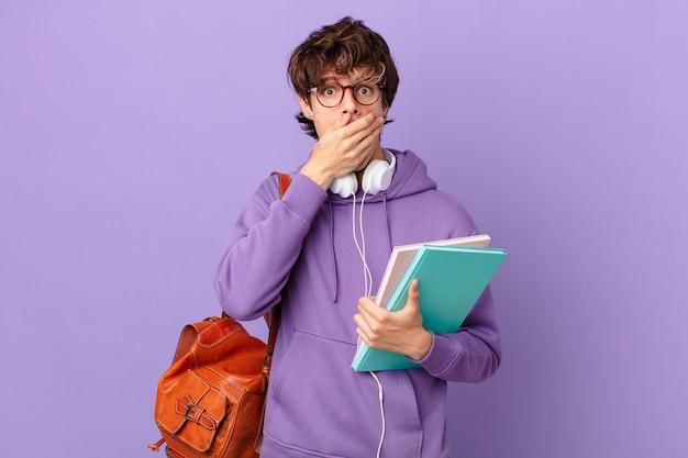 Молодой студент мужчина прикрывает рот руками с потрясенным
