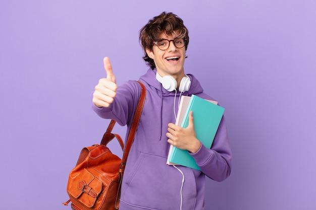 자랑스럽게 생각하는 젊은 학생 남자, 엄지손가락으로 긍정적인 미소