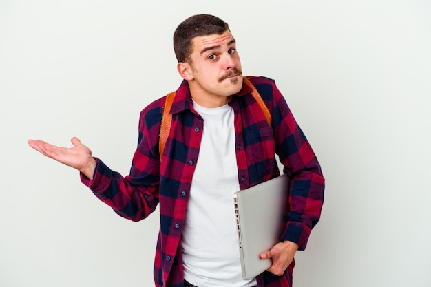 白い壁に隔離されたラップトップを持っている若い学生の男は、コピースペースを保持するために混乱し、疑わしい肩をすくめる肩をすくめる
