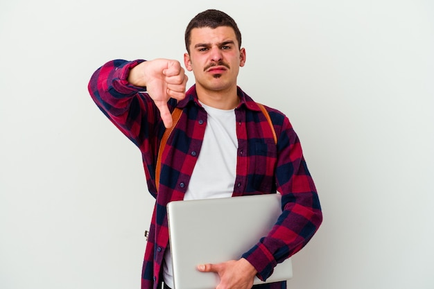 親指を下に示し、嫌悪感を表現する白い壁に分離されたラップトップを保持している若い学生男性