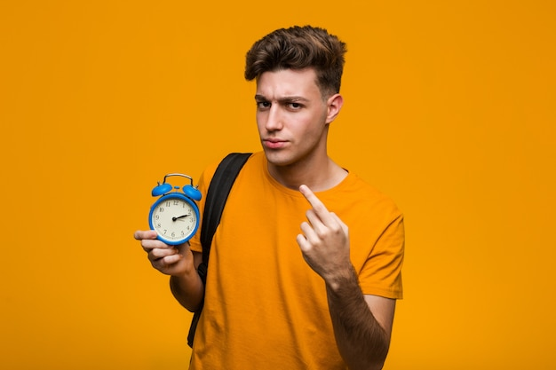 Young student man holding an alarm clock impressed holding copy space on palm.