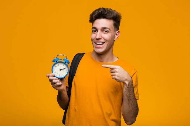 Young student man holding an alarm clock pointing with finger at you as if inviting come closer.