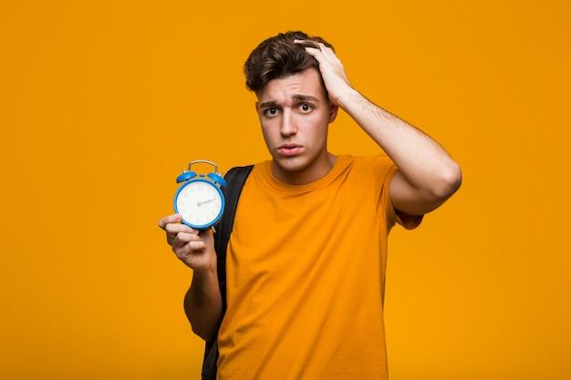 目覚まし時計を保持している若い学生男が前を向く陽気な笑顔。