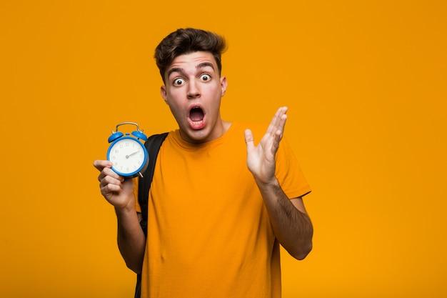 幸せ、笑顔、陽気な目覚まし時計を持って若い学生男