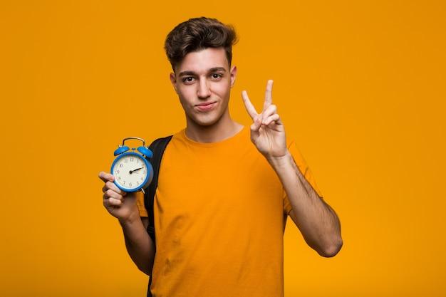 Молодой студент мужчина держит будильник, имея отличную идею, концепцию творчества.