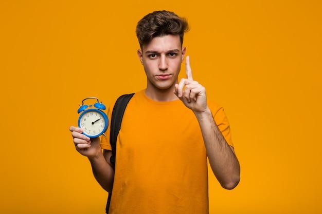 指で番号2を示す目覚まし時計を保持している若い学生男。