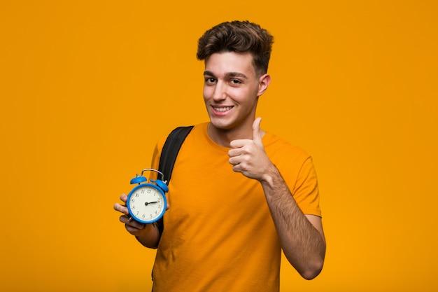 勝利のサインを示し、広く笑顔の目覚まし時計を保持している若い学生男。