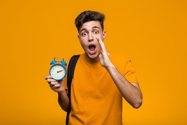 人差し指を離れて元気に指して笑顔の目覚まし時計を持っている若い学生の男。