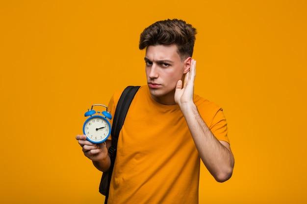 組んだ腕に自信を持って笑顔の目覚まし時計を保持している若い学生男。