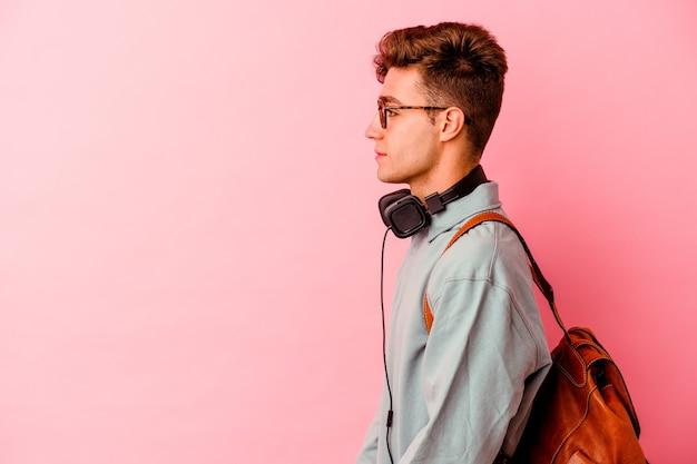 ピンクの背景に孤立した若い学生の男は、左、横向きのポーズを見つめています。