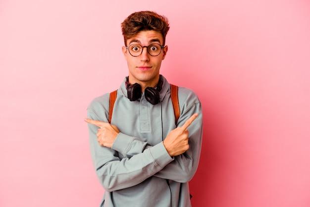 ピンクの背景ポイントで横に孤立した若い学生の男は、2つのオプションから選択しようとしています。