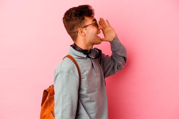 開いた口の近くで叫び、手のひらを保持しているピンクの背景に孤立した若い学生の男。