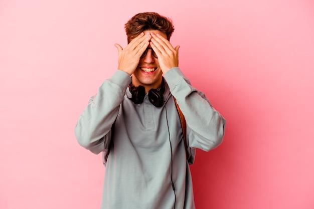 분홍색 벽에 고립 된 젊은 학생 남자는 놀람을 광범위 하 게 기다리고 미소 손으로 눈을 다룹니다.