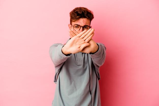 Молодой студент человек изолирован на розовой стене, делая жест отрицания