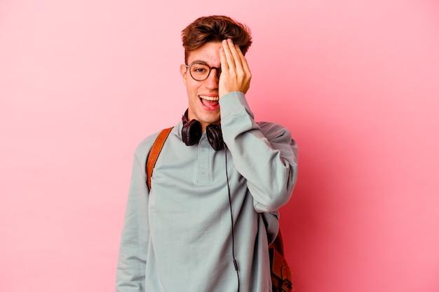 Молодой студент человек, изолированные на розовой стене, весело закрывая половину лица ладонью.