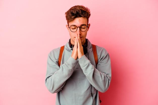 입 근처기도에 손을 잡고 분홍색 벽에 고립 된 젊은 학생 남자는 자신감을 느낀다.