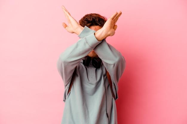 두 팔을 유지하는 분홍색 벽에 고립 된 젊은 학생 남자 넘어, 거부 개념.