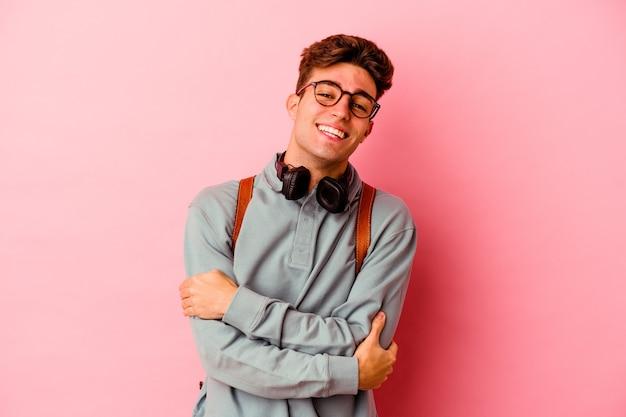 분홍색 벽 웃음과 재미에 고립 된 젊은 학생 남자