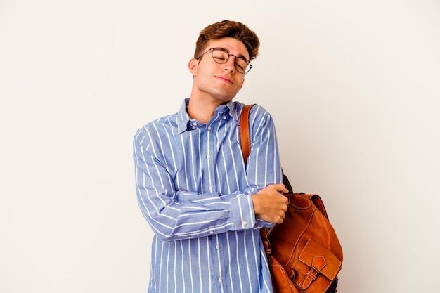 흰색 배경에 고립 된 젊은 학생 남자 포옹, 평온하고 행복 하 게 웃 고.