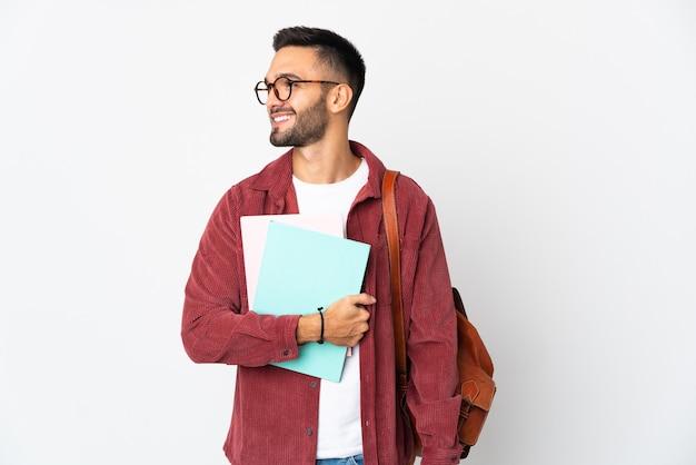 側面を見て白い背景で隔離の若い学生男