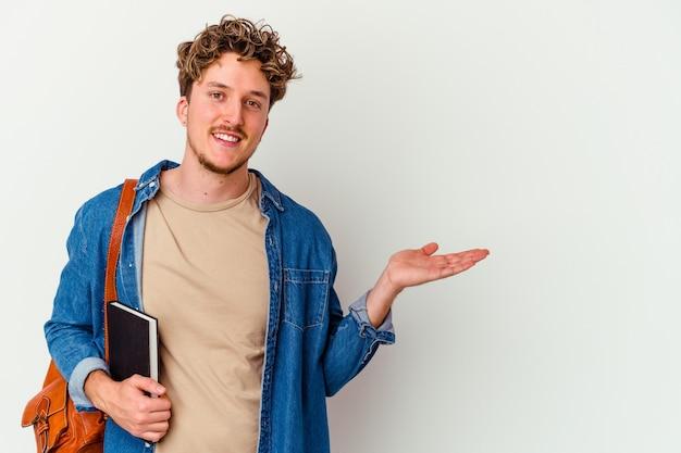 手のひらにコピースペースを示し、腰に別の手を保持している白い背景で隔離の若い学生の男。
