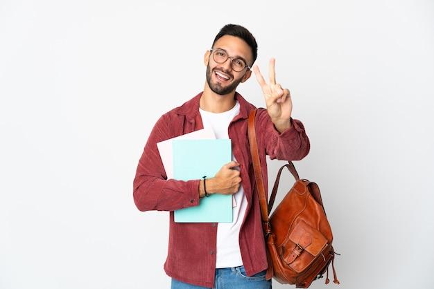 笑顔と勝利のサインを示す白い背景で隔離の若い学生男