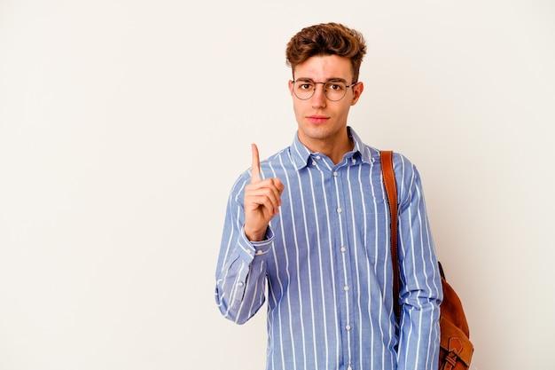 손가락으로 번호 하나를 보여주는 흰 벽에 고립 된 젊은 학생 남자.