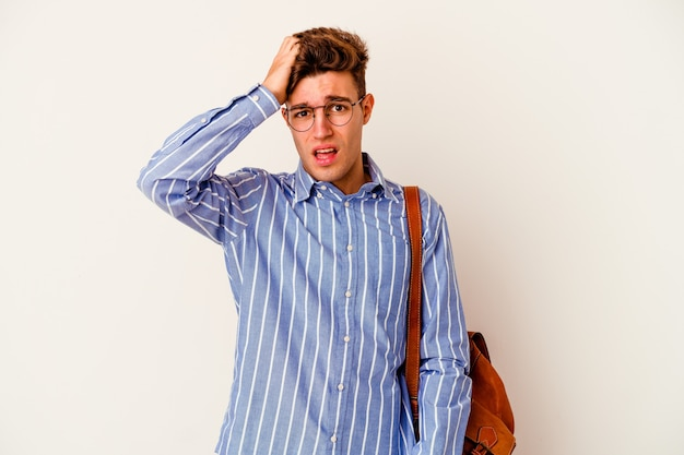 Young student man isolated on white background being shocked, she has remembered important meeting.