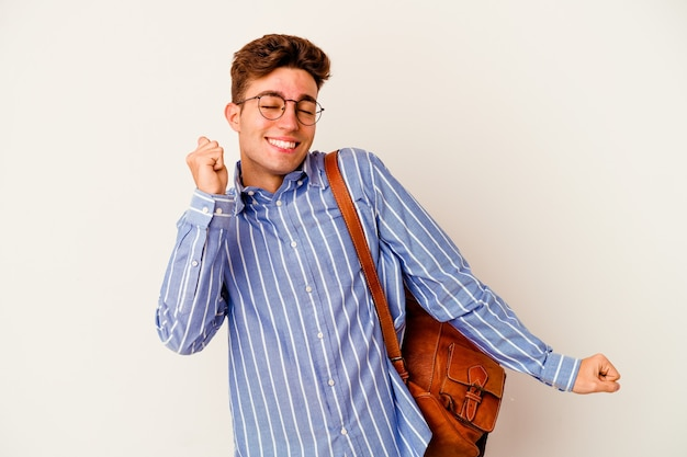 Young student man isolated on white background dancing and having fun.
