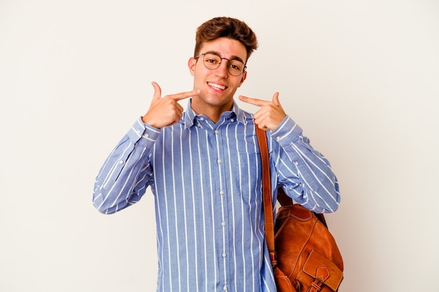 Young student man isolated on white wall smiles, pointing fingers at mouth.