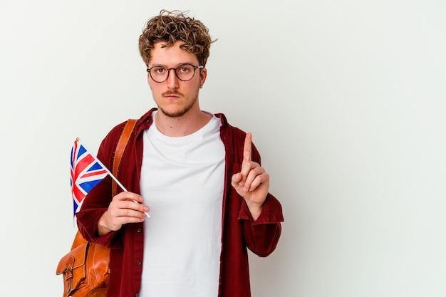 指でナンバーワンを示す白い背景で隔離の英語を学ぶ若い学生の男。